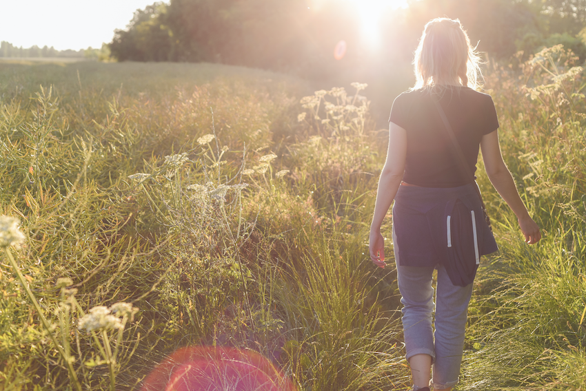 stress-relieving exercises: woman walking in meadow